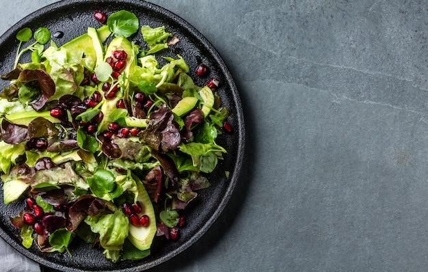 Lettuce salad with pomegranate on black plate. top view