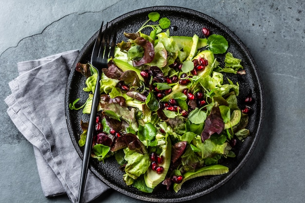 Lettuce salad with pomegranate on black plate.