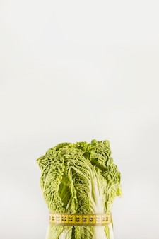 Lettuce tied with measuring tape on white backdrop