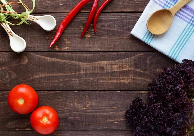 木製の背景にレタス、トマト、唐辛子。上面図。