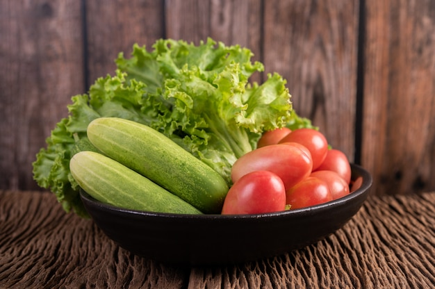 Lettuce, tomatoes, and cucumber in a black bowl on the wooden floor.