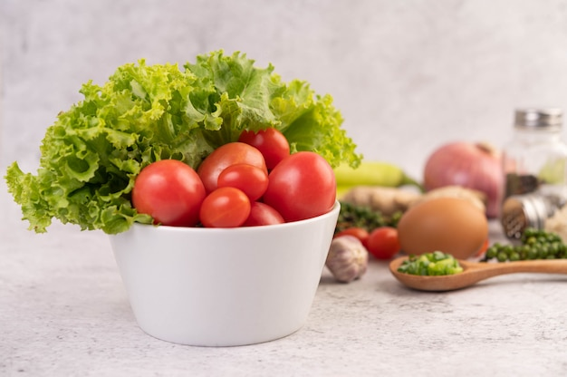 Lattuga e pomodori in una tazza bianca con cipolle affettate e peperoni freschi sul pavimento di cemento.