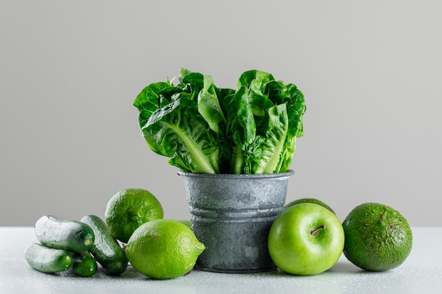 Lettuce with cucumber, lime, apple, avocado in a mini bucket on white and grey table