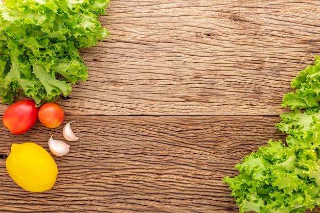 素朴な天然木の質感の背景にトマト、ニンニク、レモンとレタス、料理の材料、上面図