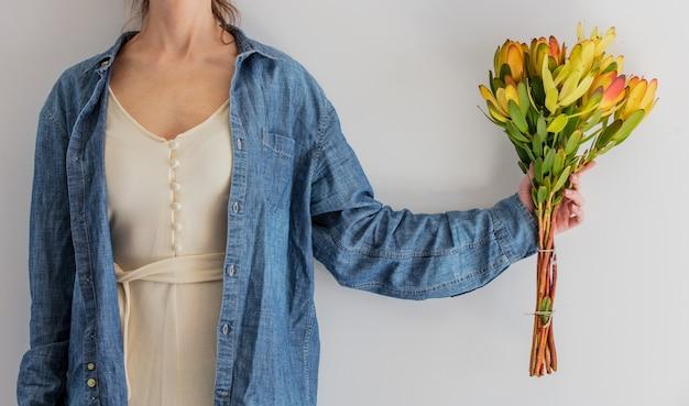 女性両手leucadendronの花束を保持