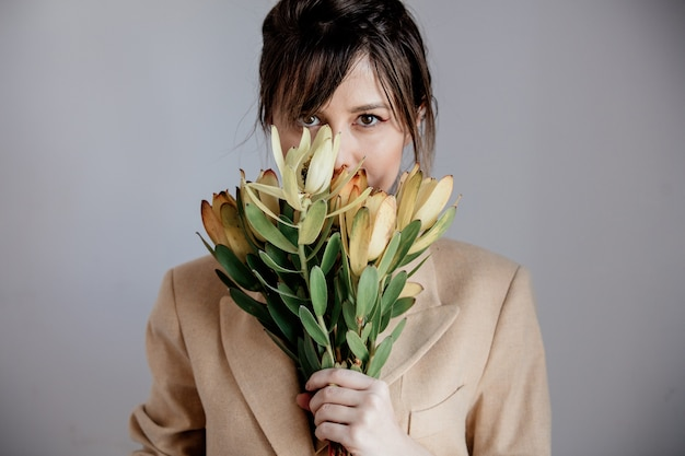 Leucadendronの花束を持つ若い女