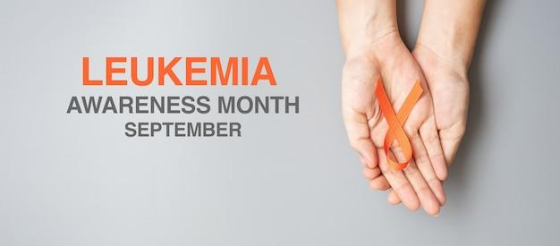 白血病啓発月間、生きている人々と病気をサポートするためのオレンジリボン。ヘルスケアと世界対がんデーのコンセプト