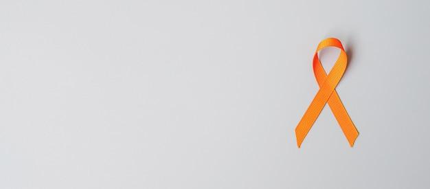 白血病、腎臓がんの日、世界の多発性硬化症、crps、自傷行為防止月間、生きている人々と病気をサポートするためのオレンジリボン。ヘルスケアと世界対がんデーのコンセプト