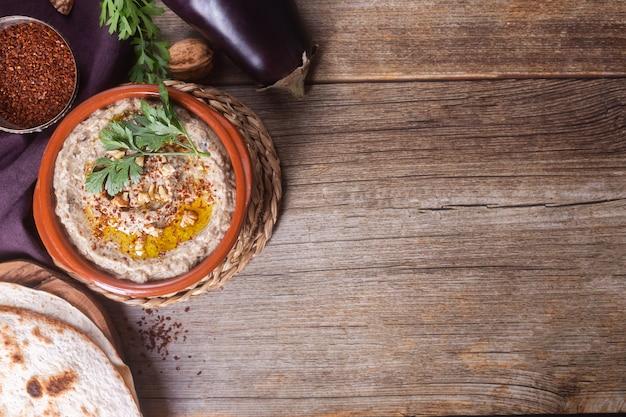 Закуска левантийской кухни из запеченных баклажанов и кунжутной пасты с оливковым маслом, специями, травами и грецкими орехами на деревянном фоне на подставке. вид сверху, копировать пространство