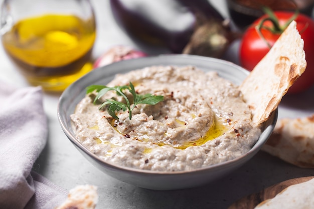 Levantine cuisine baba ganoush snack with stuck pita bread poured with olive oil with ingredients in the background