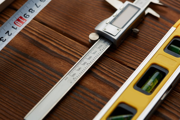 레벨과 캘리퍼스, 나무 테이블. 전문 측정기, 목수 장비, 목공 도구