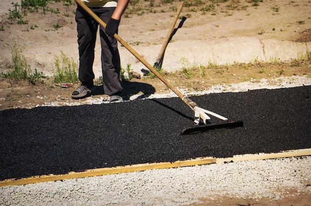 Выравнивание свежего асфальта на небольшой трассе. укладка асфальта, ремонт дорог.
