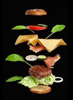 Levitating cheeseburger ingredients: juicy meat cutlet, cheddar cheese, sesame bun, lettuce, white onion rings, slice of tomato, cucumber on black background. fast food floating in the air