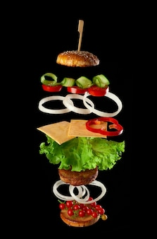 Levitating cheeseburger ingredients: juicy meat cutlet, cheese, sesame bun, lettuce, white onion rings, slice of tomato, cucumber on black background. fast food floating in the air