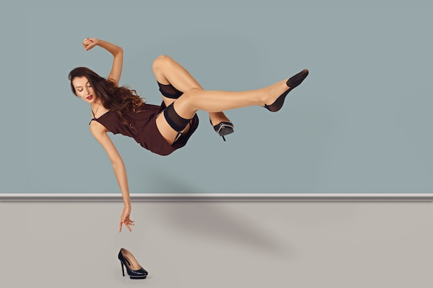 Levitating girl in short dress and stockings reaching her hand for a shoe on a floor