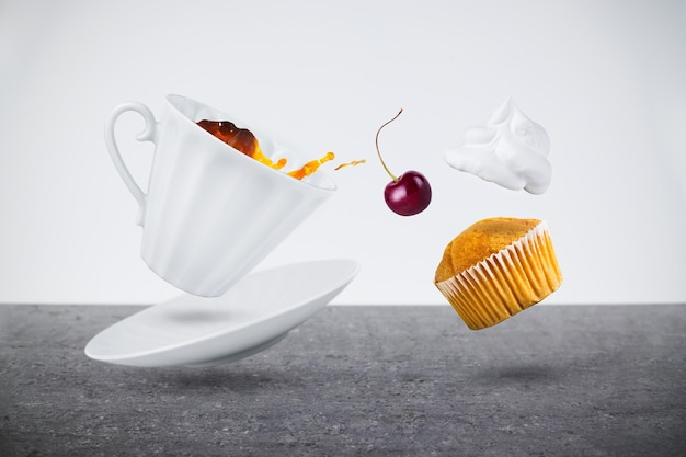 Levitation of white porcelain cup with tea or coffee and saucer, cupcake with cream and cherry over gray granite table