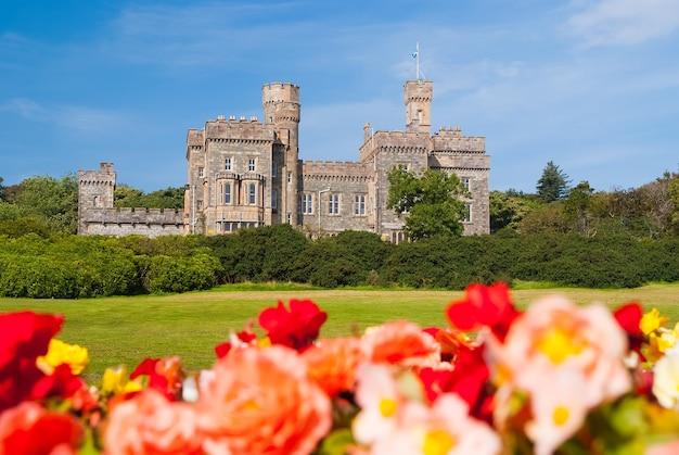 手前にぼやけたバラがあるイギリス、ストーノウェーのリューズ城。青い空に緑の敷地がある城。歴史的な建築とデザイン。ランドマークと魅力。島の夏休み。