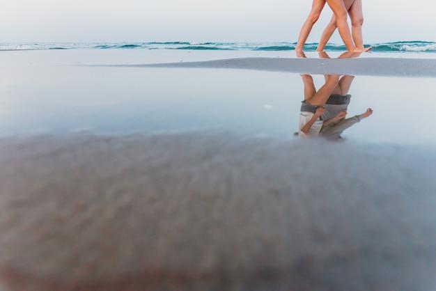 Lgbtのビーチを歩いている恋に2人のレズビアンの女性のカップル。