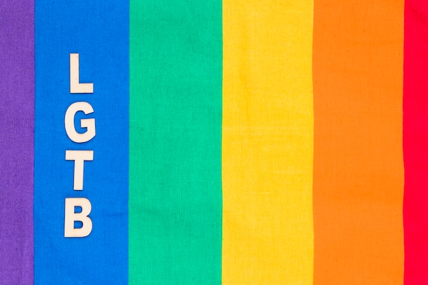 Lgbt abbreviation on blue stripe of rainbow background