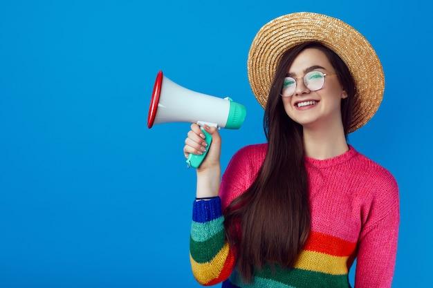 Лгбт-активистка в радужном свитере говорит в мегафон и улыбается