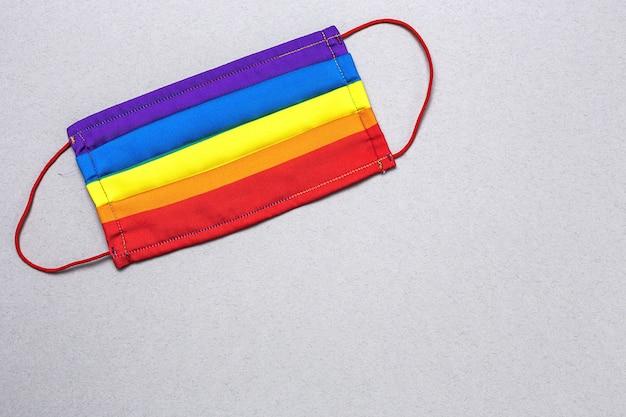 上から虹色の保護フェイスマスクとlgbtの背景。フラットレイ。 covid-19ウイルス