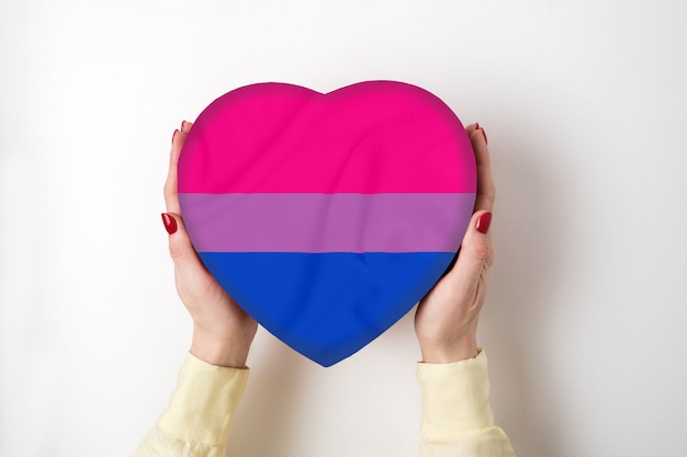 Lgbt bisexual pride flag on a heart shape box in female hands. pride symbol. top view
