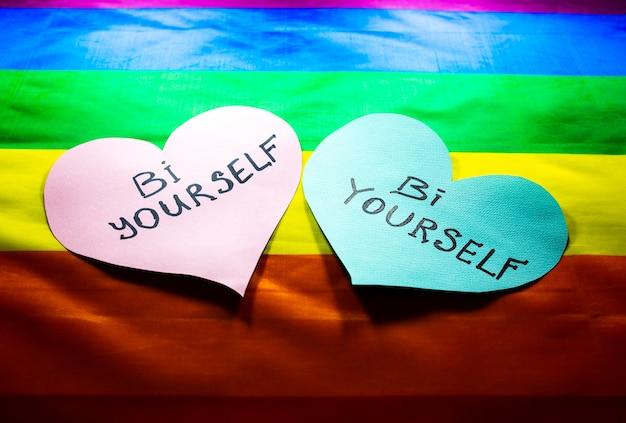 Lgbt 커뮤니티 다채로운 플래그입니다. bi 자신은 무지개 배경에 마음에 서명합니다. 레즈비언, 게이 및 양성애자 문제. 동성애 성향이 있는 커플의 결혼 합법화.