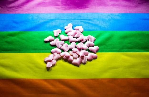 Lgbt 커뮤니티 다채로운 플래그. 무지개 바탕에 핑크 하트 심장입니다. 레즈비언과 게이 문제. 동성애 성향을 가진 커플의 결혼 합법화.