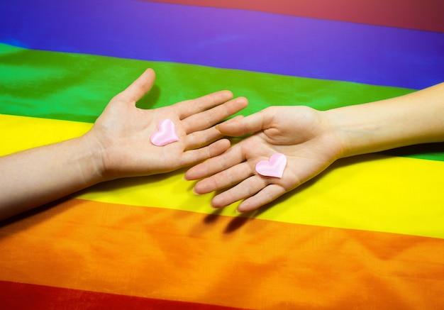 Lgbt 커뮤니티 다채로운 플래그입니다. 무지개 배경에 두 여자의 손입니다. 레즈비언과 게이 문제. 동성애 성향이 있는 커플의 결혼 합법화.