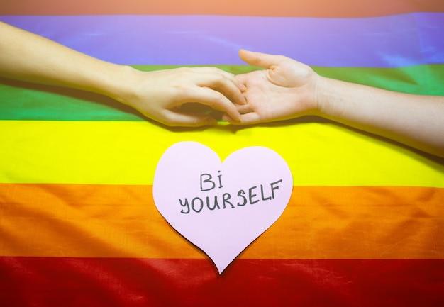 Lgbtコミュニティのカラフルな旗。虹の背景に2人の女性の手。レズビアンとゲイの問題。同性愛指向のカップルのための結婚の合法化。