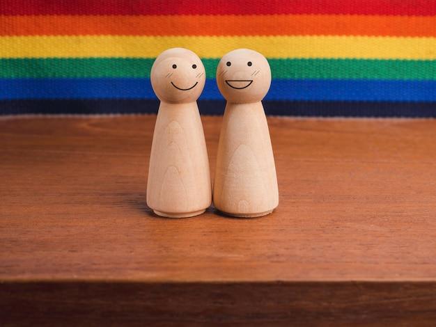 Lgbt 커플 개념입니다. 치마 모양의 두 나무 인물, 행복한 미소 얼굴이 무지개 깃발 배경의 나무 탁자에 함께 서 있습니다. lgbt 프라이드 기호입니다.