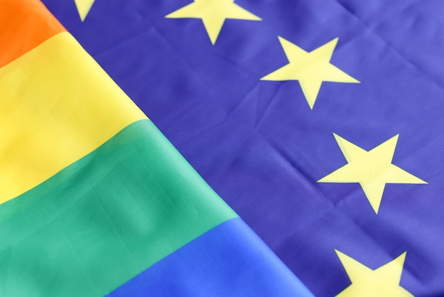 Lgbt and eu flag lying side by side closeup background. sexual minorities concept