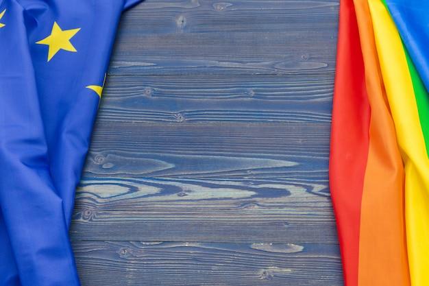 Lgbt and eu flag together on wooden background