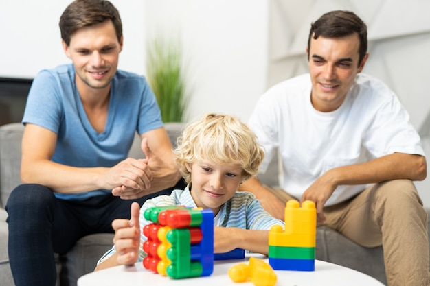 Семья лгбт, гей-пара с приемным сыном - гомосексуальные родители с ребенком веселятся дома