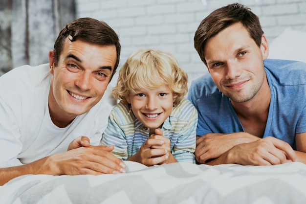 Lgbt family, gay couple with adopted son - homosexual parents with their kid having fun at home