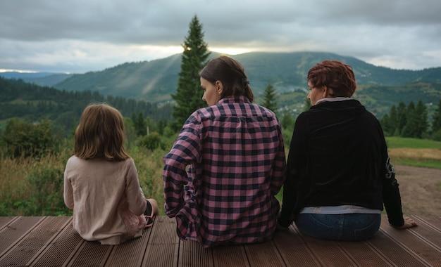 어린 소녀가 야외 테라스에 앉아 산에서 일몰을 바라보는 lgbt 가족