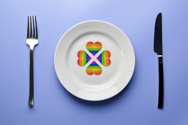 Сердца флага лгбт на тарелке со столовыми приборами