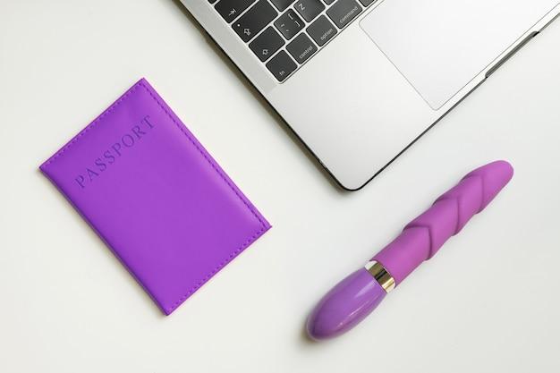 Флаг лгбт на паспорт, фаллоимитатор и ноутбук. концепция путешествия лгбт.
