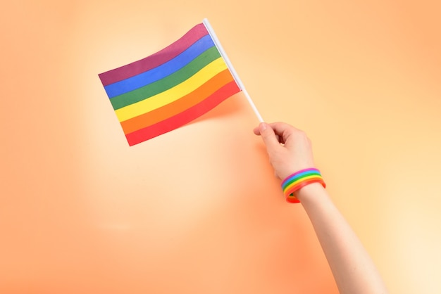 Lgbt flag in woman hand on orange background. copy space.
