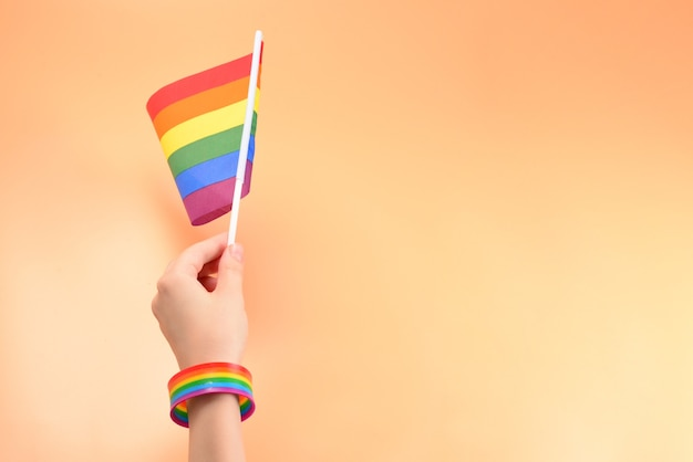 Lgbt flag in woman hand on orange background. copy space. Premium Photo