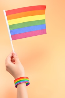 Lgbt flag in woman hand on orange surface