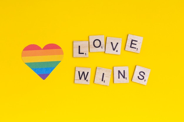 Lgbt heart icon and word love wins on wooden blocks