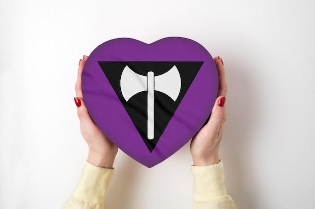 Флаг лгбт-сообщества лесбиянок на коробке в форме сердца в женских руках. символ гордости вид сверху