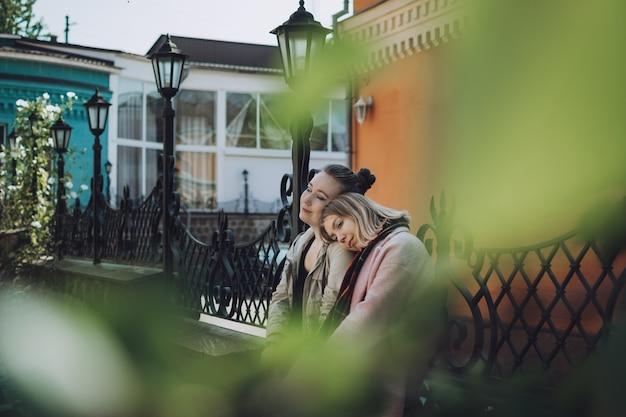 Lgbtレズビアンカップルの愛の瞬間の概念2人の若いレズビアンの女の子が抱き締めて屋外を幸せに歩く