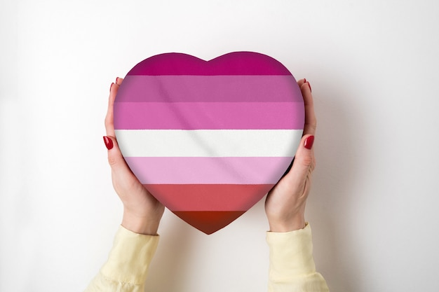 Флаг гордости лгбт на коробке в форме сердца в женских руках. символ гордости вид сверху