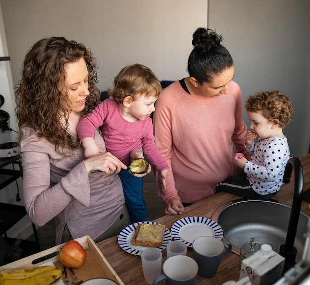 Lgbt mothers at home spending time in the kitchen with their children