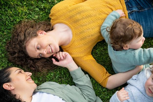 公園の外で子供たちが芝生でリラックスしているlgbtの母親