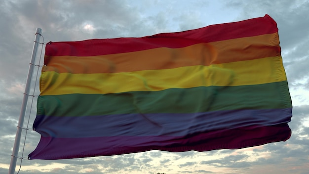 Lgbt pride flag waving in the wind against deep beautiful sky at sunset