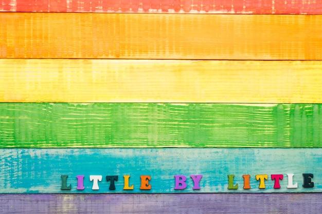 Lgbtの虹色、木製の背景、少しずつ碑文、右下隅、コピースペース、フラットレイ、上面図