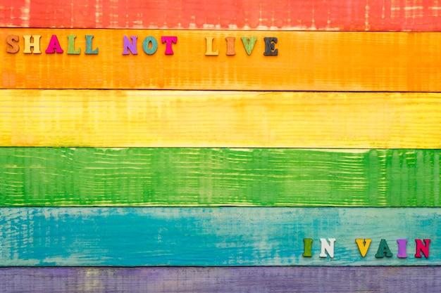Лгбт-цвета радуги, деревянный фон, с надписью не должны дожить до рамки и зря внизу; копия пространства, вид сверху